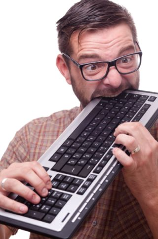 Man biting keyboard